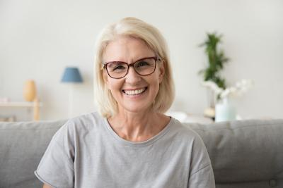 older woman with glasses smiling l dental implants wilmington