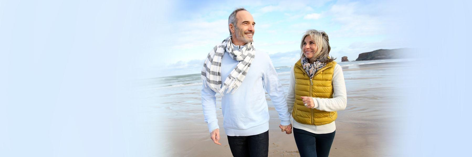 older couple smiling walking on a beach l Drs. Gladnick and Justison pike creek de