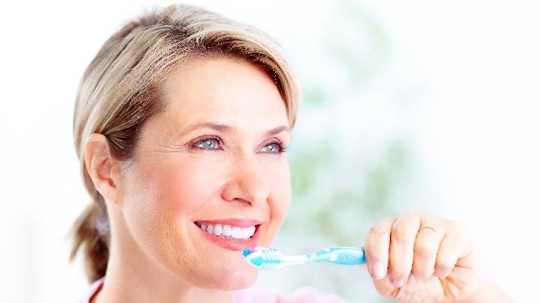 Woman Brushing Teeth | Dentist in Wilmington DE