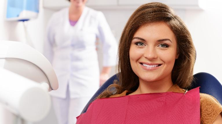 A Woman Smiles Sitting In The Dental Chair | Wilmington Dentist