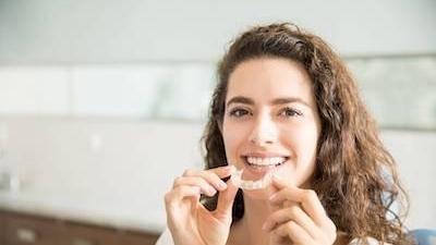 Woman holding clear aligner l Invisalign Pike Creek DE